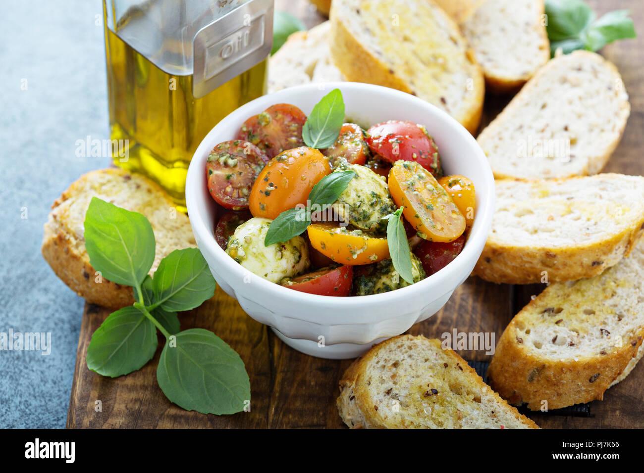 Caprese bruschetta with cherry tomatoes, mozarella and basil pesto - Stock Image