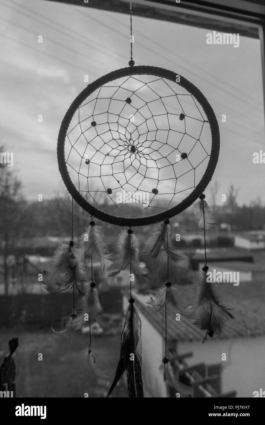 Dreamcatcher hanging at window black and white - Stock Image