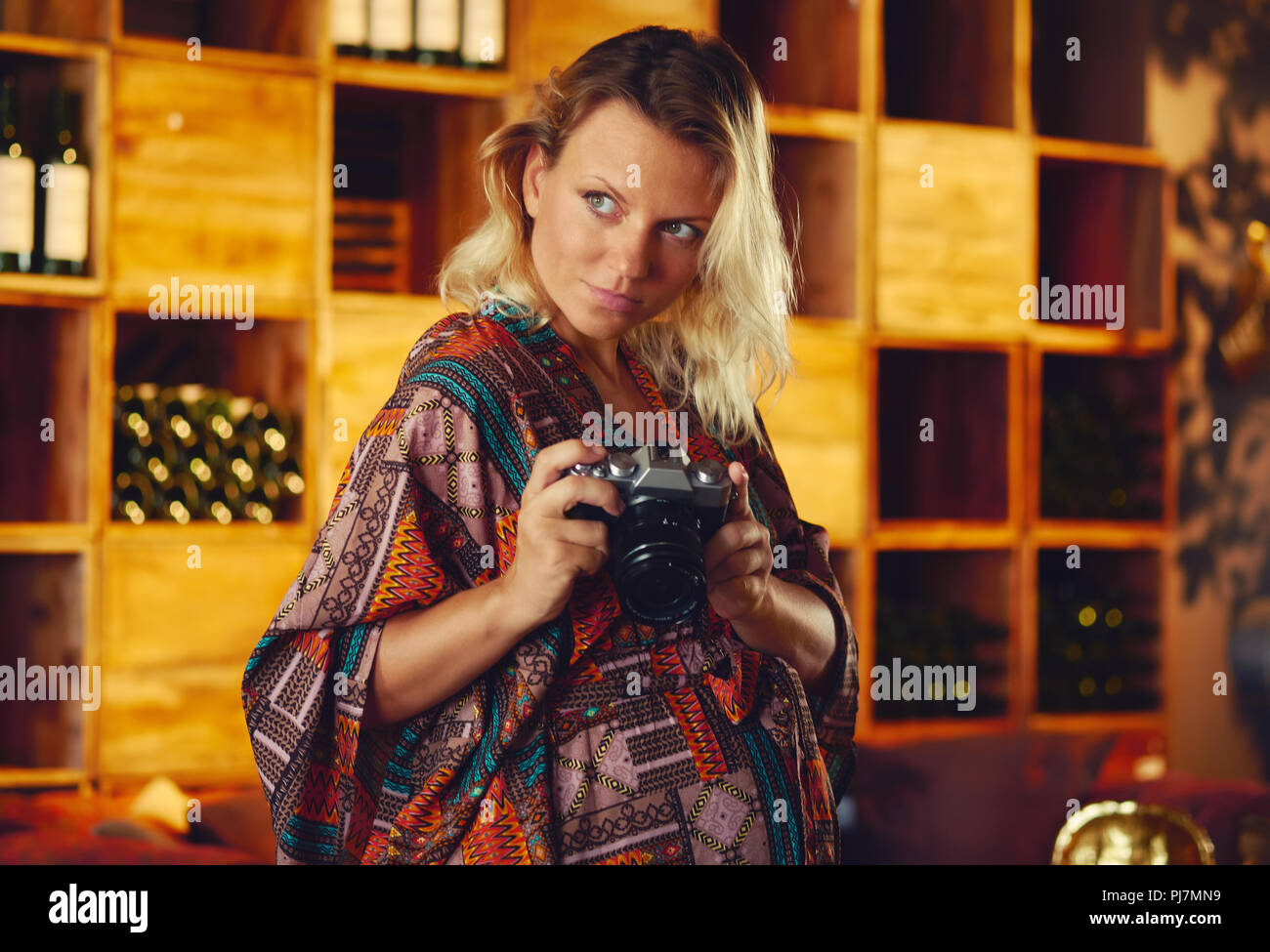 Portrait of a young pregnant pensive blond woman holding photo camera and looking away, wine chiller cabinet on a background. Photographer female posi - Stock Image