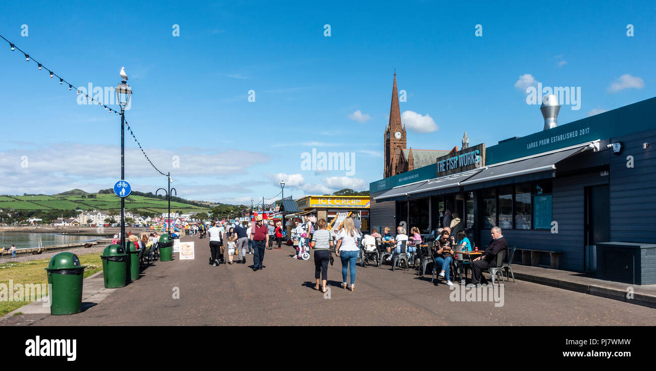 Largs promenade on a warm, sunny early September day. Fish and chips, ice cream, people strolling, - Stock Image