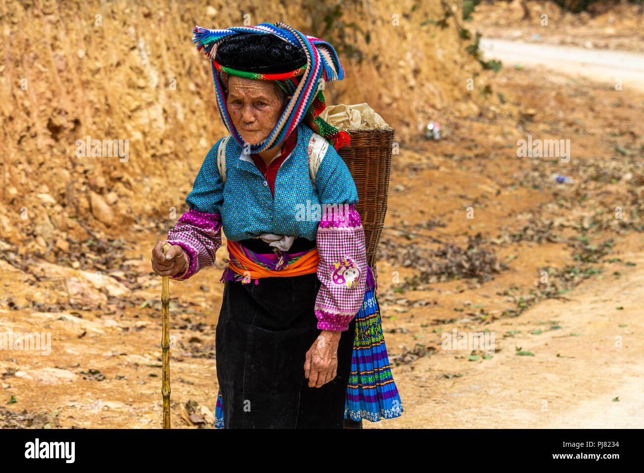 Ha Giang, Vietnam - March 18, 2018: Woman walking on a dusty road near agricultural fields in northern Vietnam Stock Photo