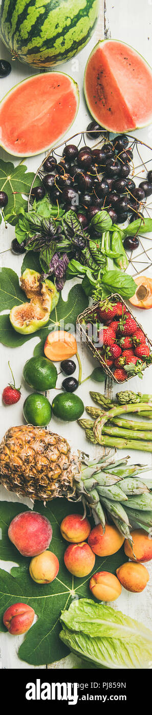 Summer food background. Flat-lay of seasonal fruit, vegetables and greens over white wooden background, top view. Vegetarian, vegan, dieting, clean ea - Stock Image