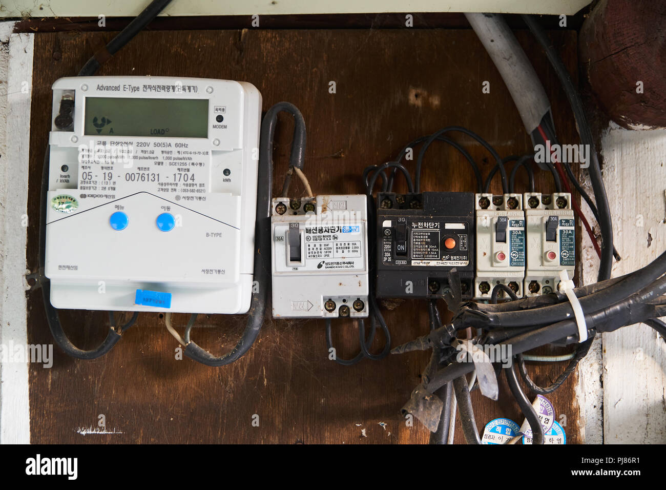 inje gun korea may 10 2018 old wires circuit breaker and digital smart electricity meters installed on a wooden board of old house in korea PJ86R1 inje gun, korea may 10, 2018 old wires, circuit breaker and