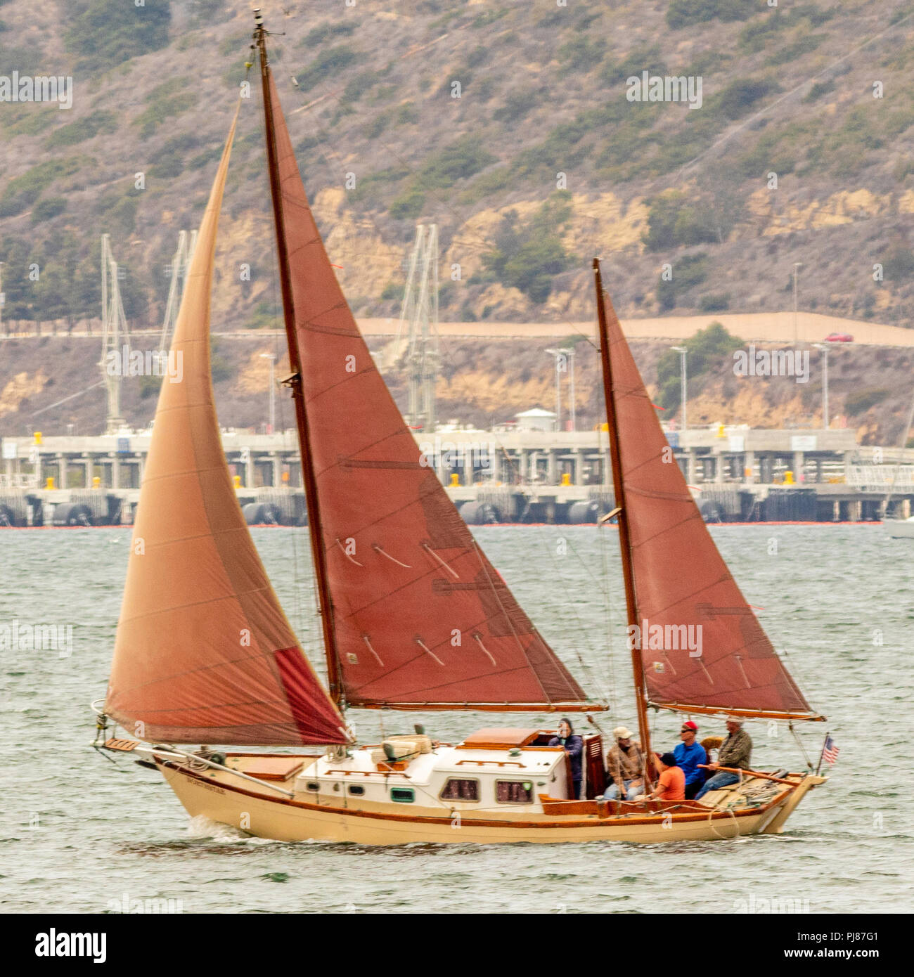 A classic ketch with tanbark sails, works upwind on a fine day - Stock Image