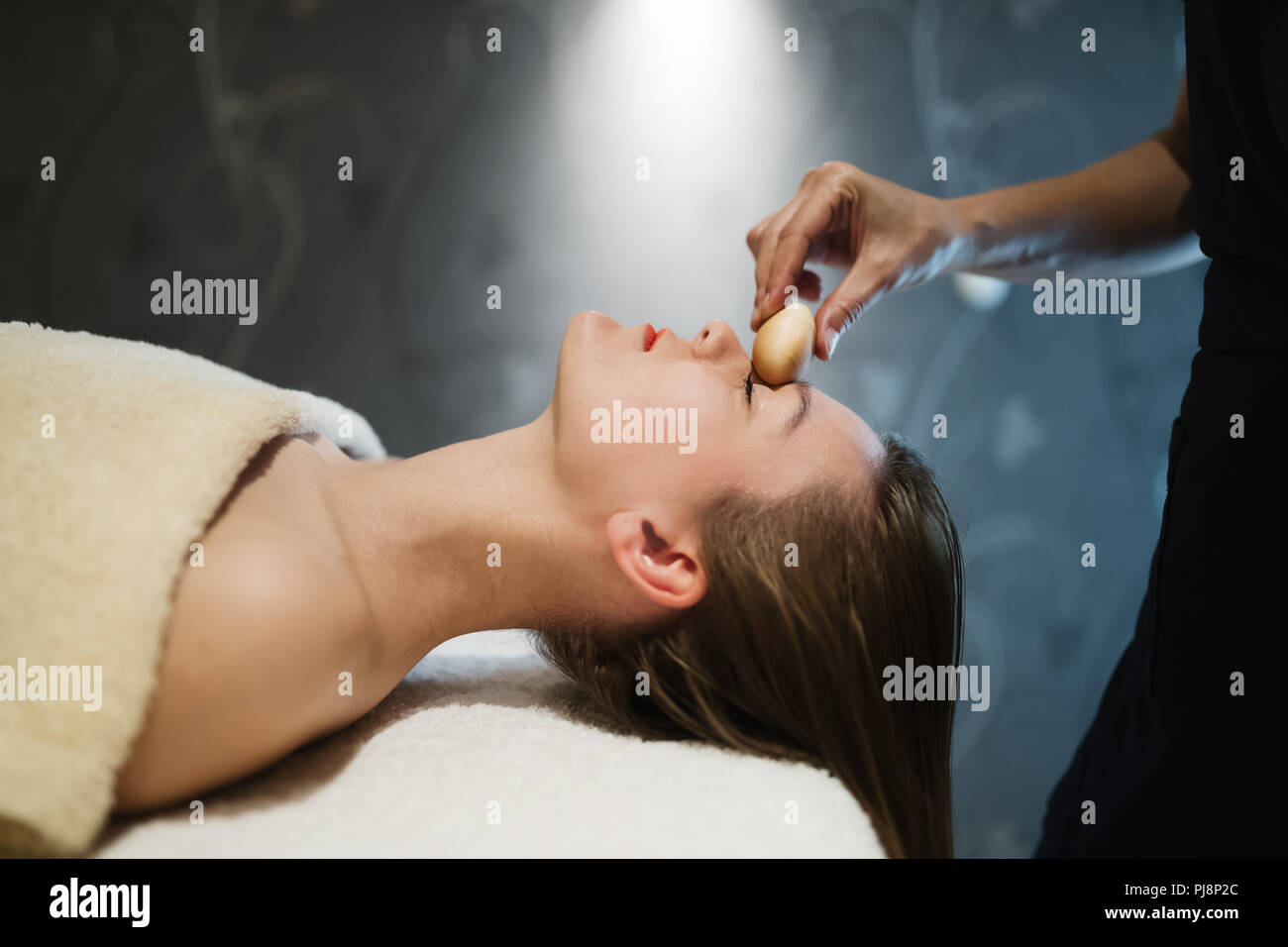 Masseur massaging face with heated objects - Stock Image