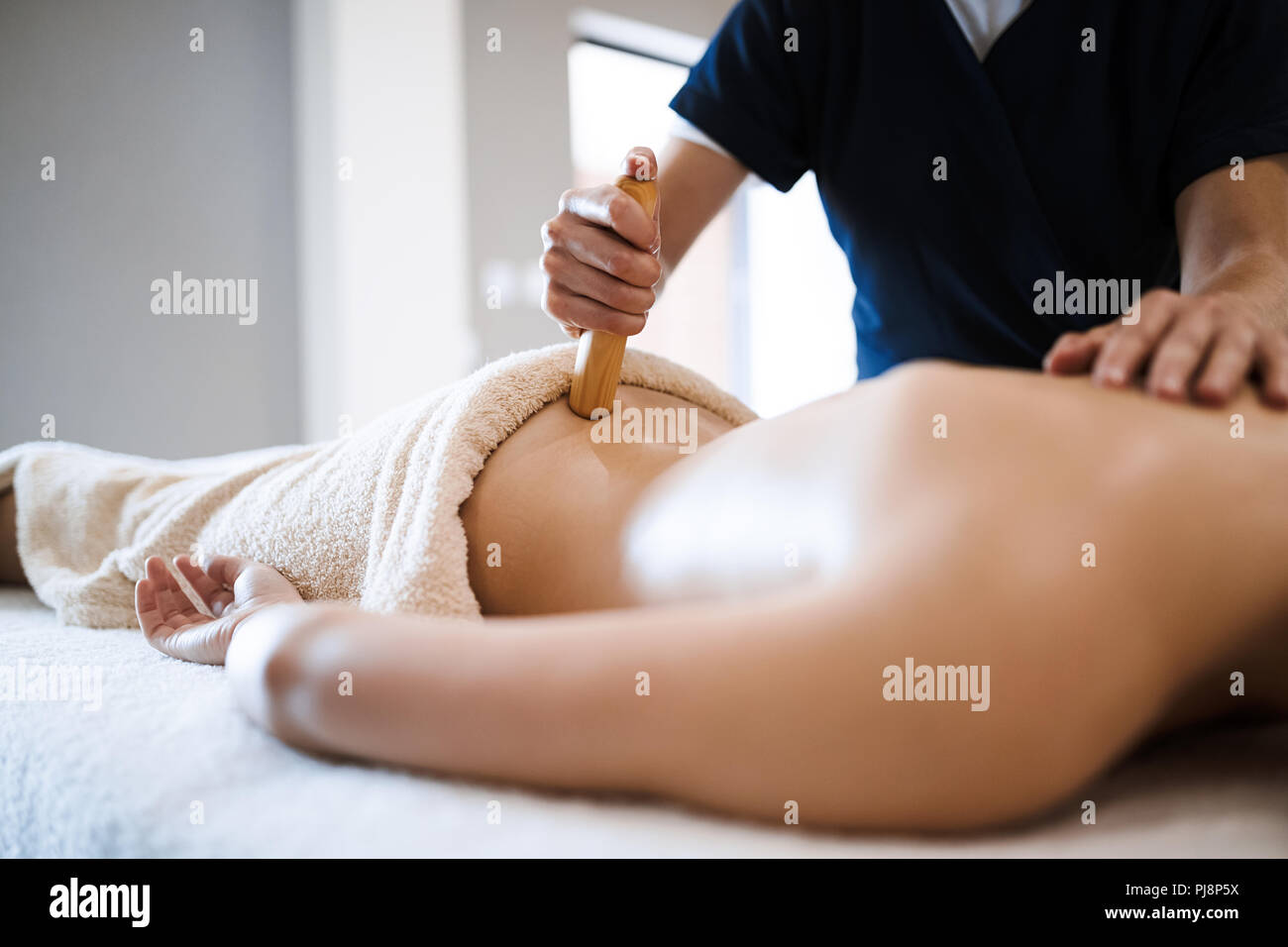 Masseur treating masseuse at wellness saloon Stock Photo