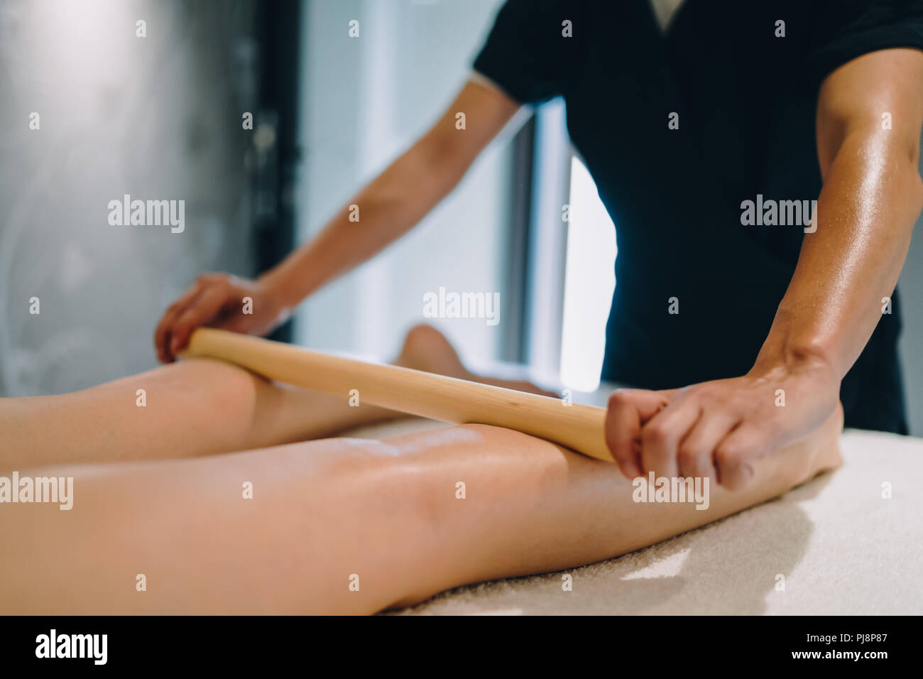 Masseur massaging masseuse during therapeutic tretment - Stock Image