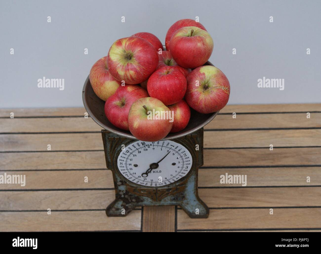 Red apples on an old-time kitchen scale seen from above - Stock Image
