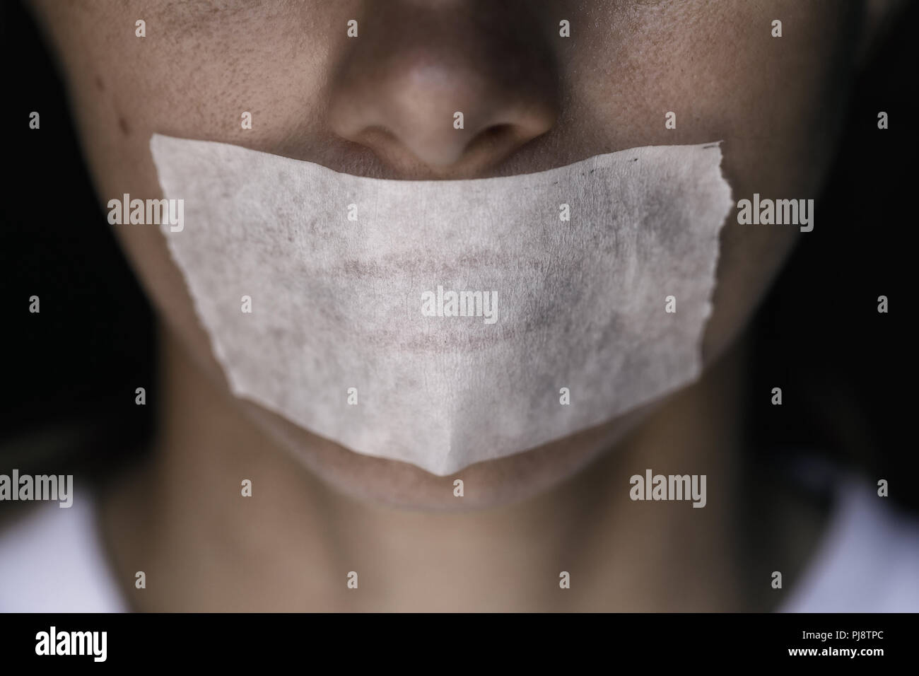 Censorship in the Modern World: A man's mouth sealed with an adhesive tape, close-up - Stock Image