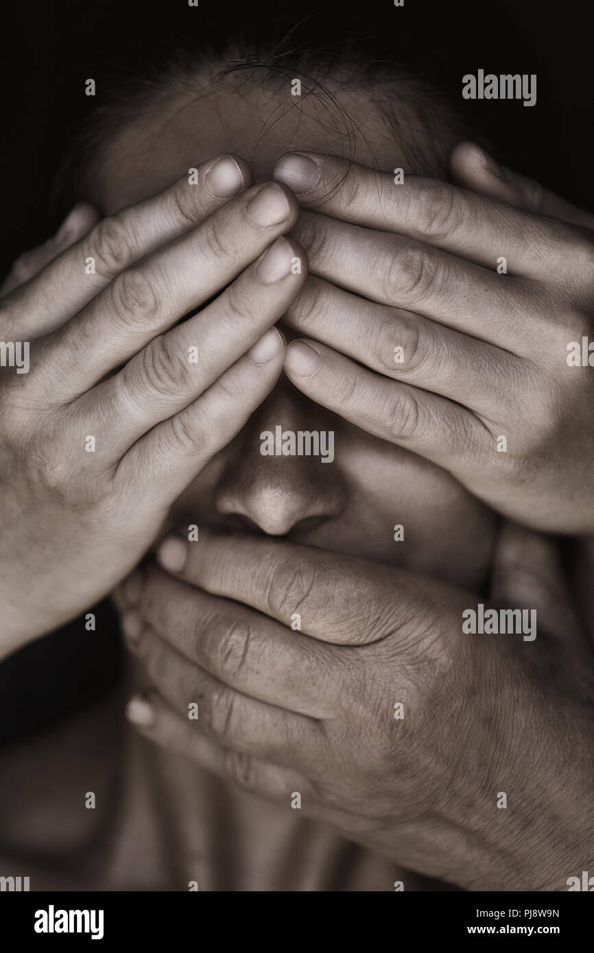 Girl face is closed by people hands, close-up - Stock Image