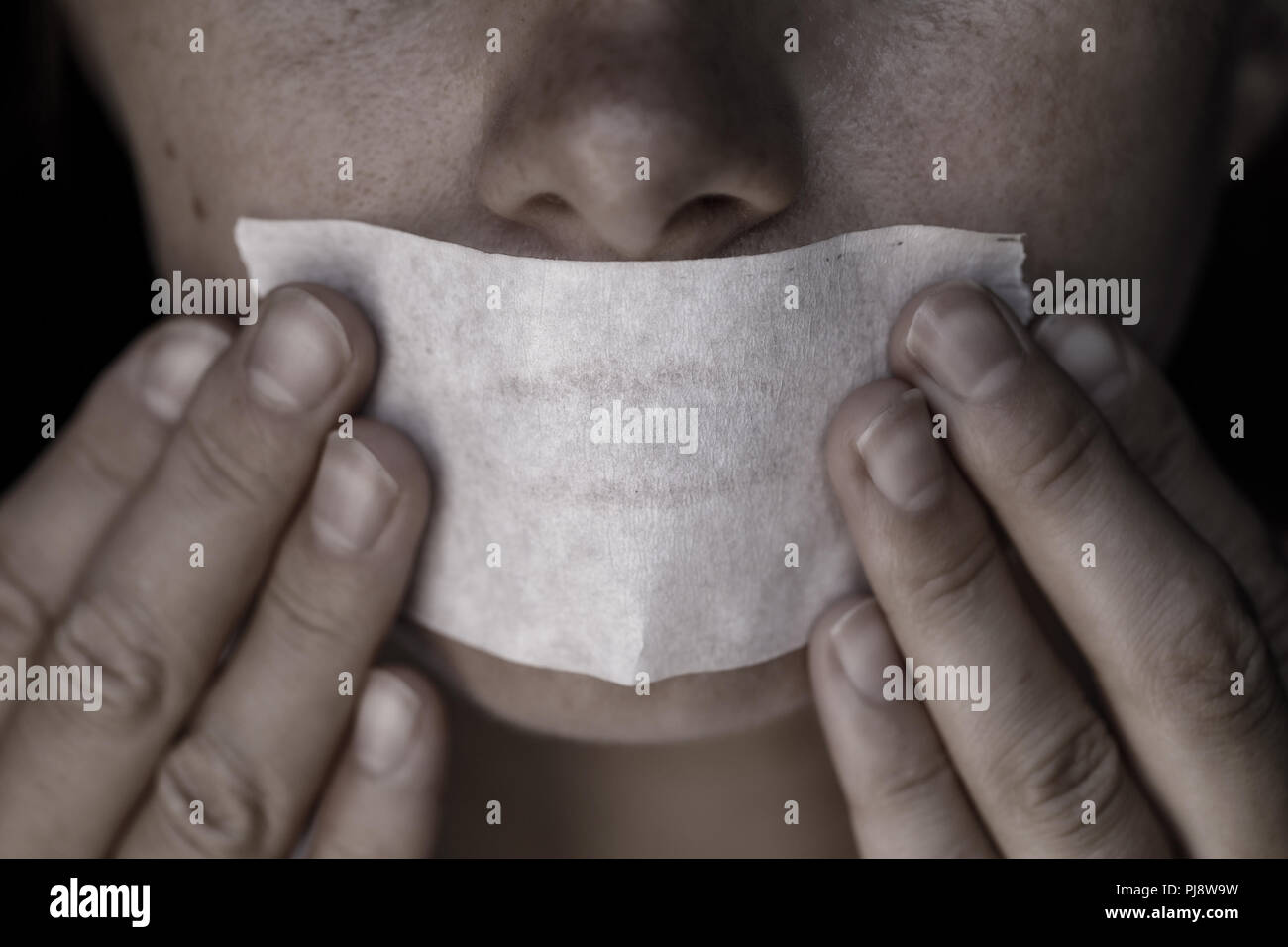 Concept on the topic of freedom of speech: the girl's face is sealed with scotch tape Stock Photo