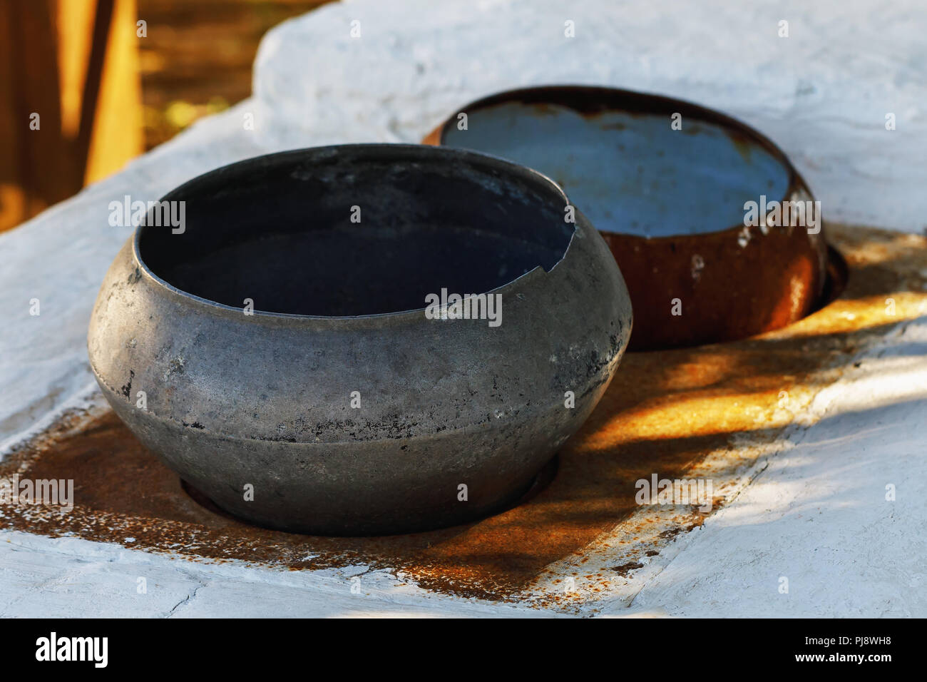 Old rustic cast iron standing on the stove, close-up - Stock Image