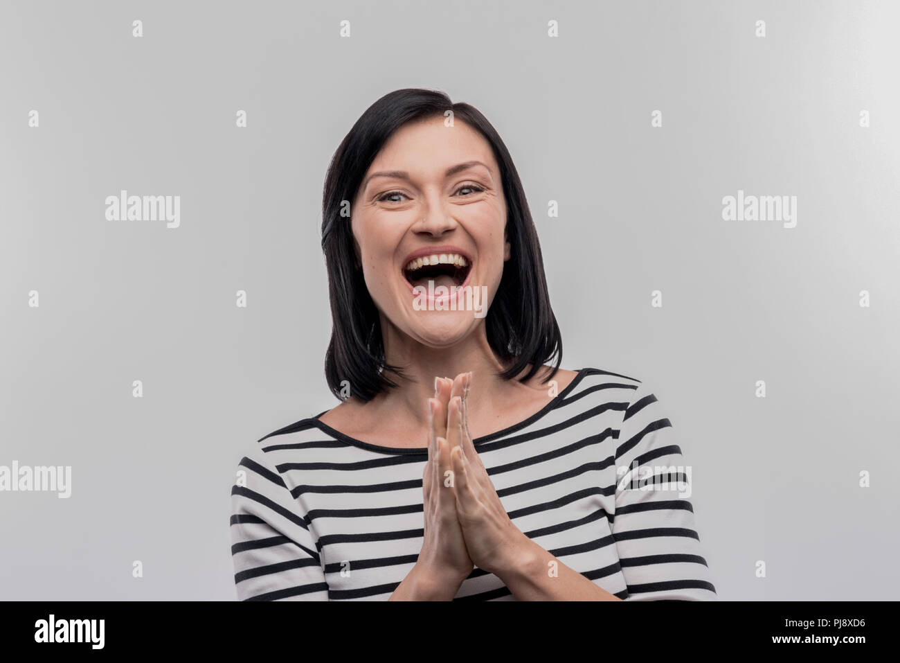 Happy beautiful woman feeling very thankful for good help - Stock Image