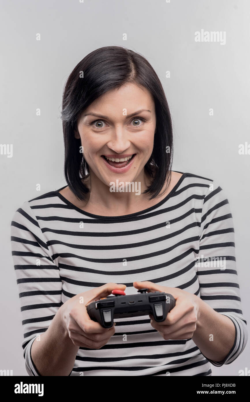 Excited woman feeling curious while holding joystick for video games - Stock Image