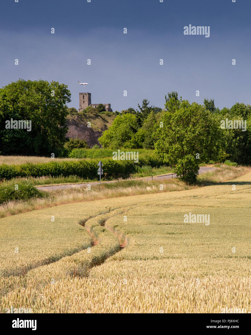 Breedon, England, UK - July 3, 2018: An aeroplane on the approach to landing at East Midlands Airport passes behind the hilltop Priory Church of Breed - Stock Image