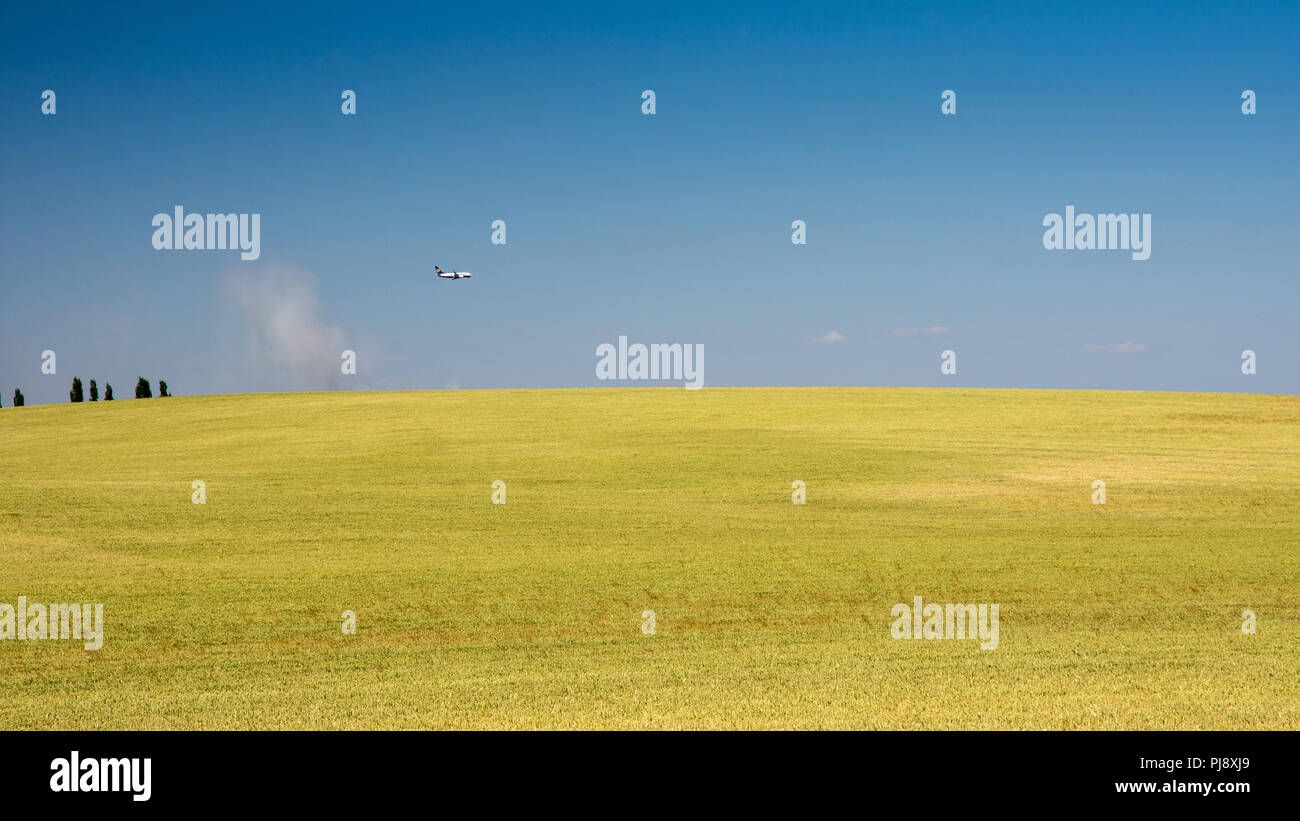 Leicestershire, England, UK - July 3, 2018: A Ryanair flight approaches East Midlands Airport over a rolling field of wheat near Breedon on the Hill o - Stock Image