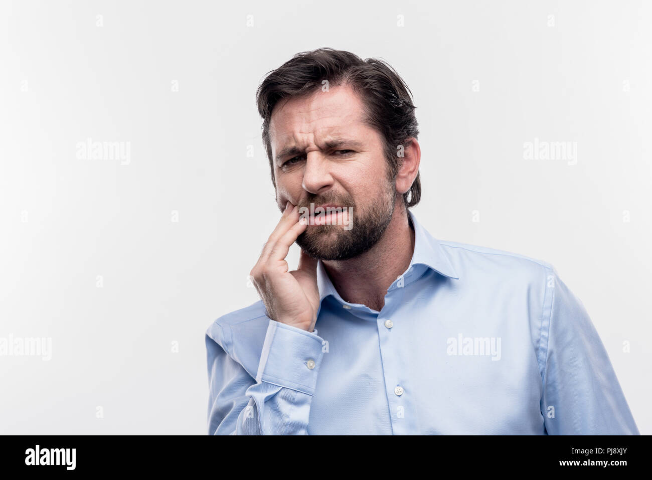 Bearded mature dark-haired businessman suffering from toothache - Stock Image
