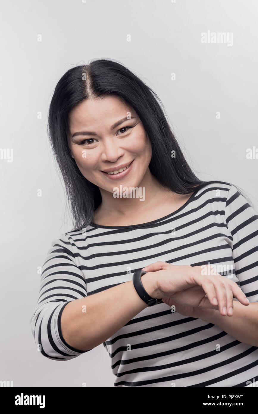Busy prosperous businesswoman checking time on her watch - Stock Image