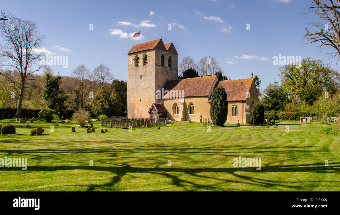 Sun shines on the tower of the 12th century Norman church of St Bartholomew in the village of Fingest, nestled under England's Chiltern Hills in Bucki Stock Photo