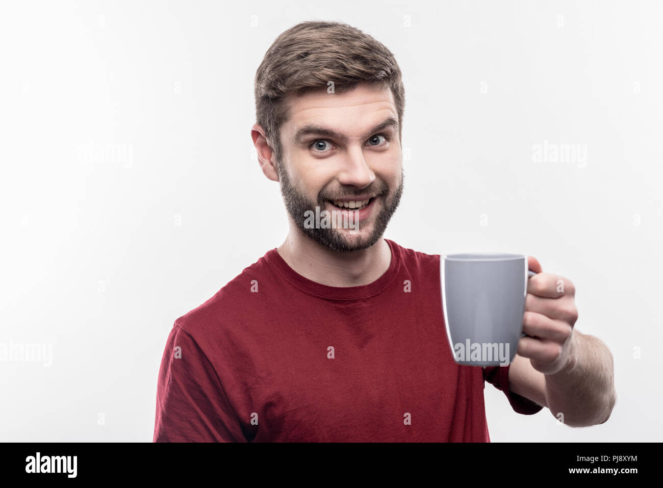 Handsome bearded man holding blue cup with freshly brewed coffee - Stock Image