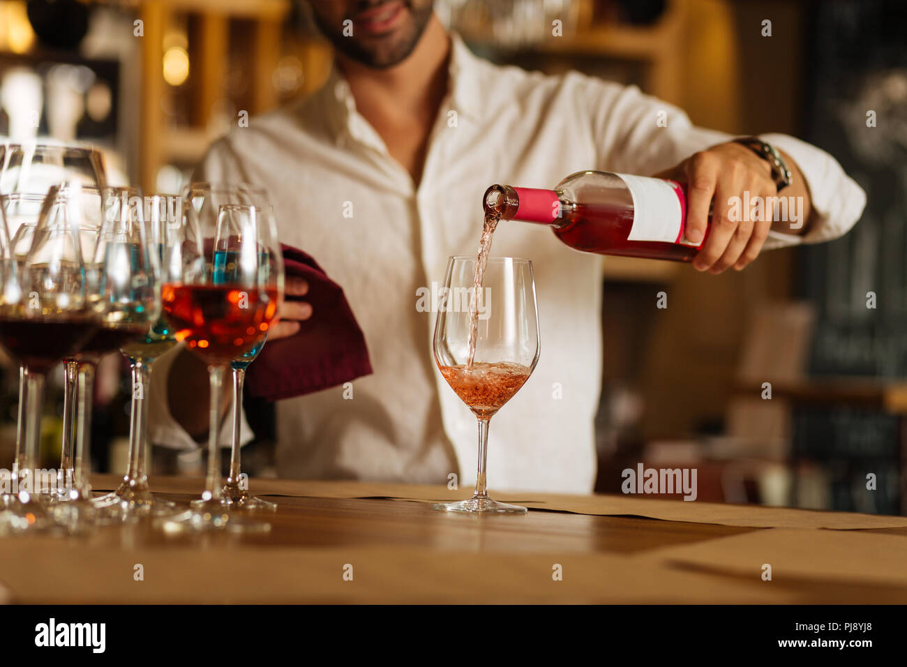 Rose wine being poured in the glass - Stock Image