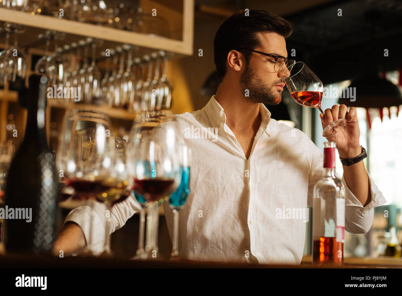 Smart serious man feeling the smell of wine - Stock Image