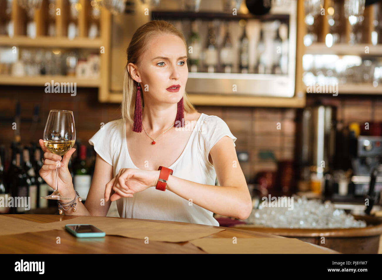 Sad cheerless woman waiting for her friend - Stock Image