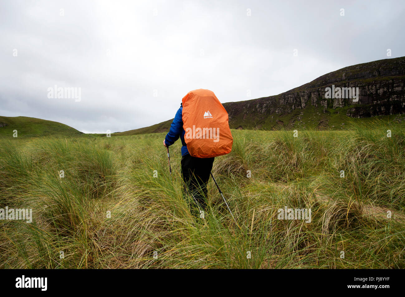 Scotland. Sutherland. Sandwood Bay. Solitary walker with protective cover on his backpack. - Stock Image