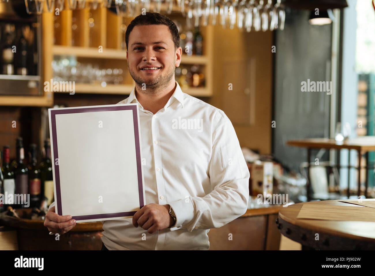 Professional nice male sommelier holding his diploma Stock Photo