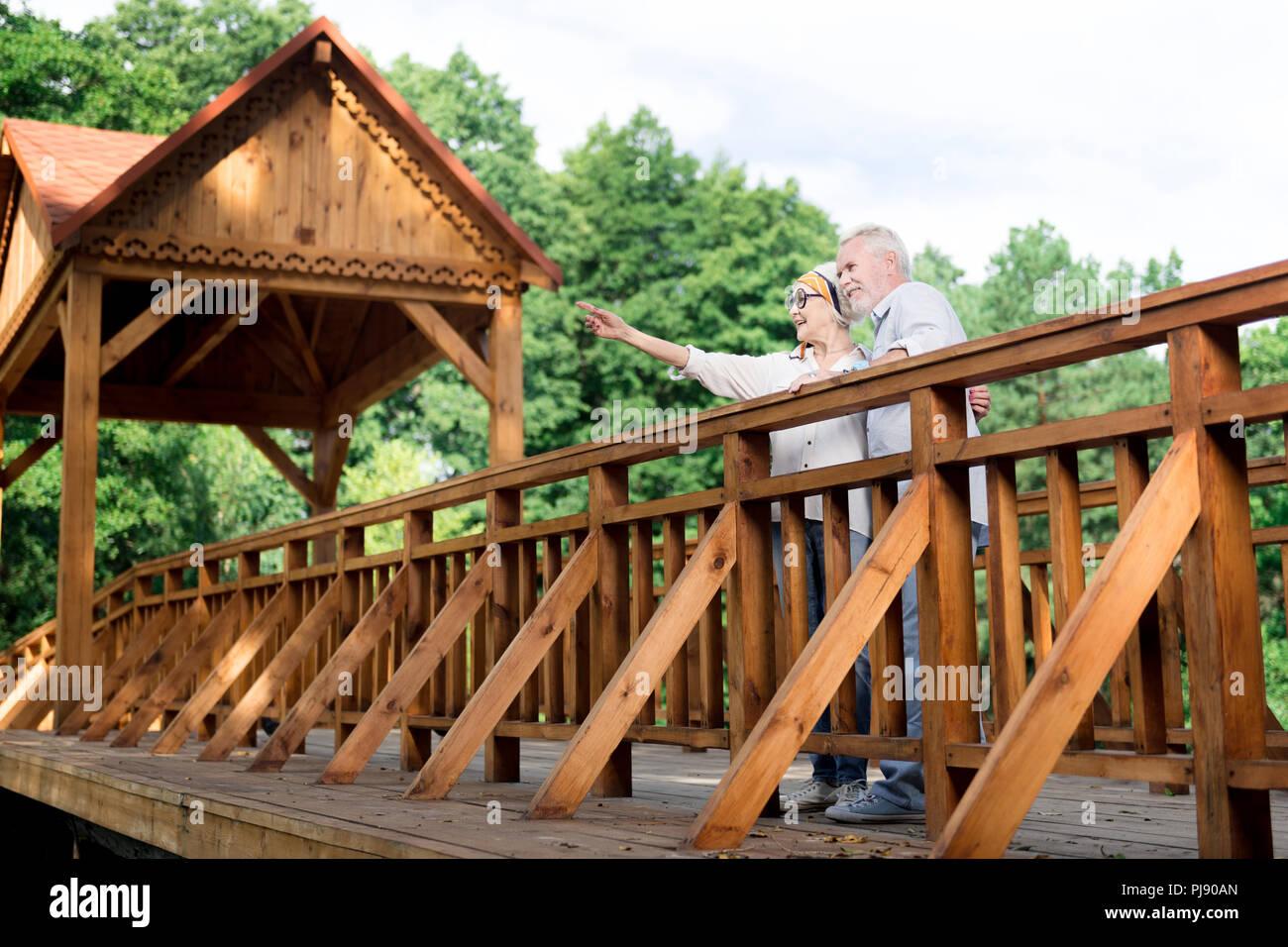 Couple of senior personalities standing on big wooden bridge - Stock Image