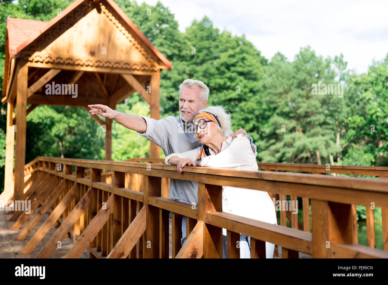 Handsome elderly man showing his appealing wife nice spot in the park - Stock Image