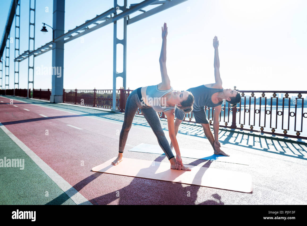 Tranquil woman and trainer working on stretching - Stock Image