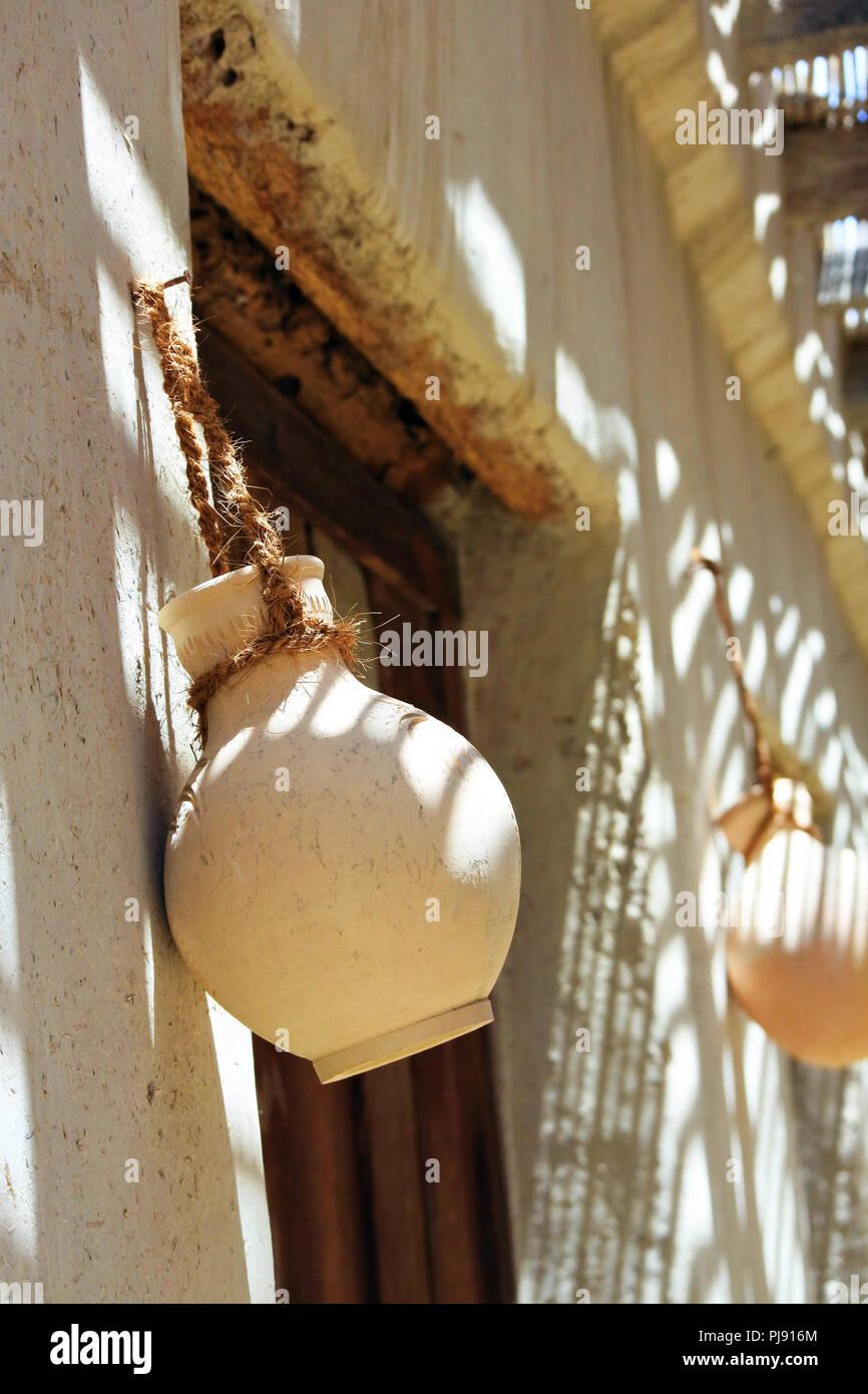Heritage,Arabic,Old,Vintage ,Pot, Hanging Pot, Door, Old Pots, Pots, Mud Pot,Clay Pots, Old House,Pots hanging on the door, Shadow, Sun Light - Stock Image