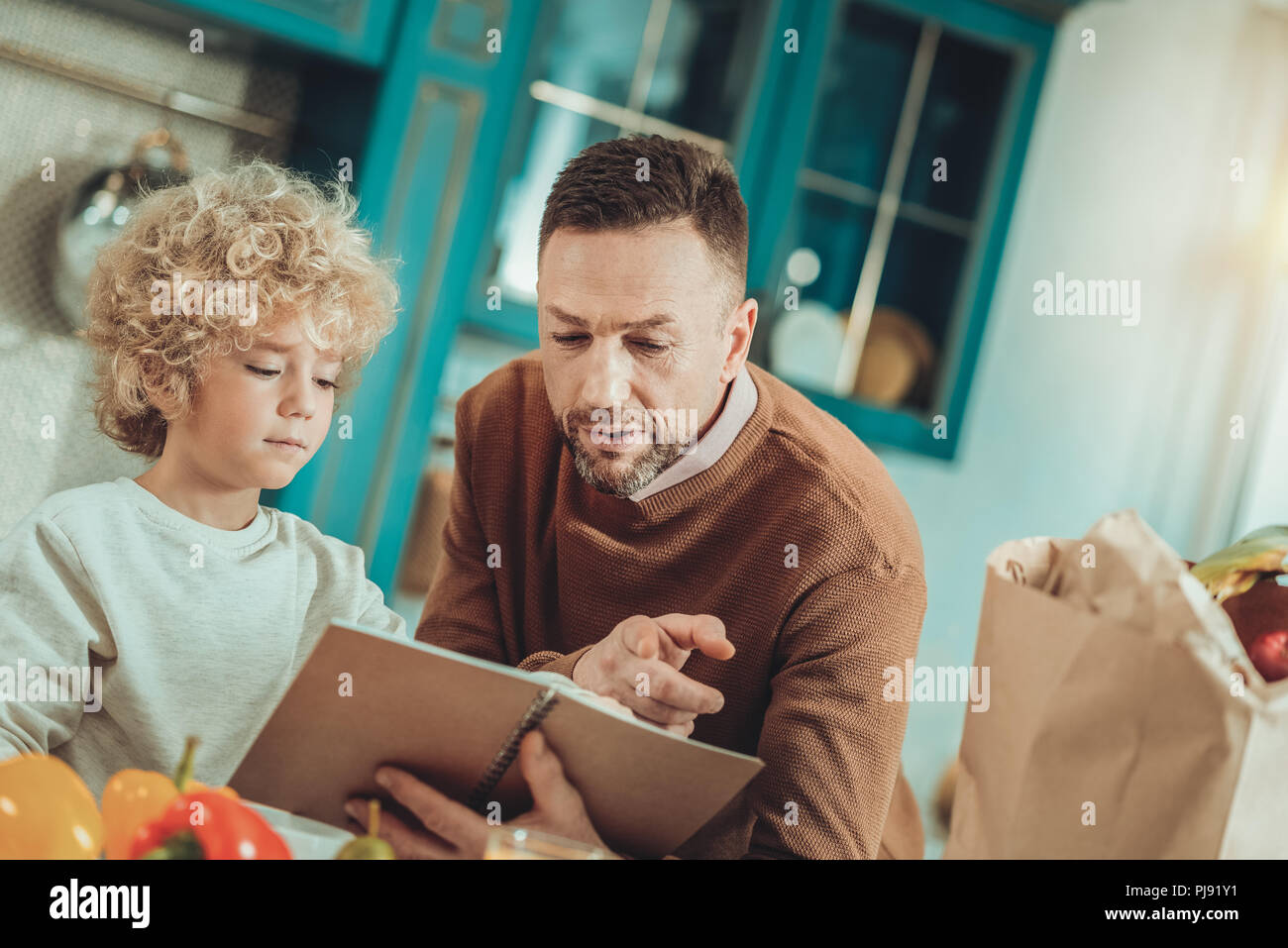 Man and the child reading a recipe - Stock Image