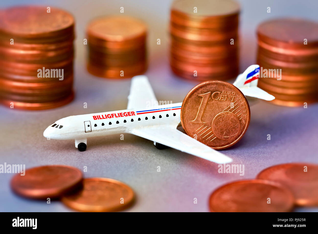 Miniature airplane with label Cheap airman and cent coins, Miniaturflugzeug mit Aufschrift Billigflieger und Centmünzen Stock Photo