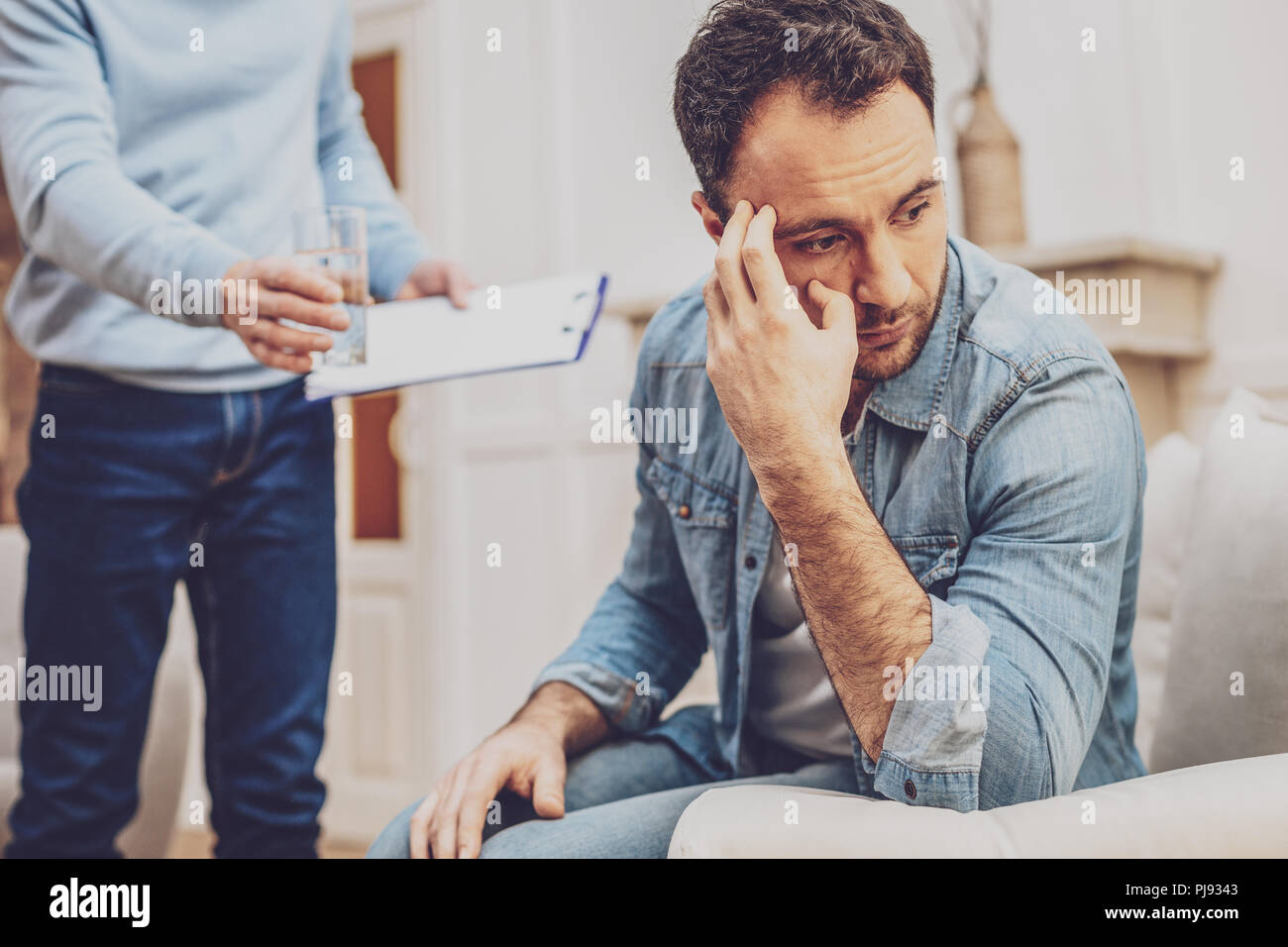 Unhappy cheerless man touching his forehead - Stock Image