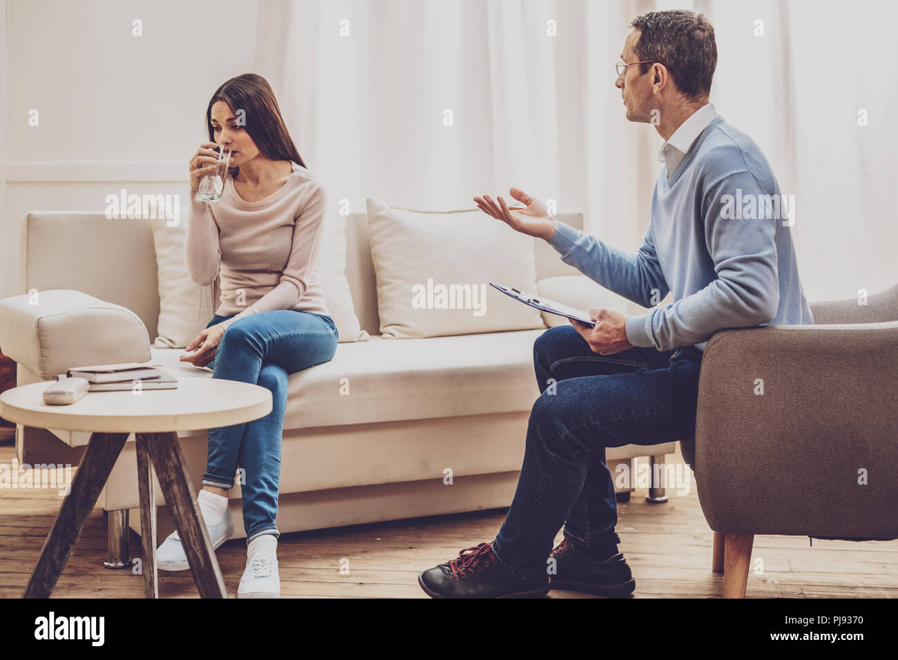 Professional male therapist helping his patient - Stock Image