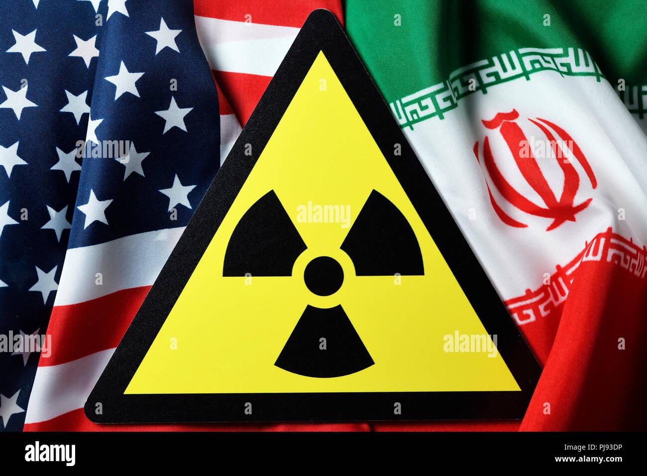 Flags of the USA and Iran and radioactivity warning, Iranian nuclear agreement, Fahnen von USA und Iran und Radioaktivität-Warnschild, iranisches Atom Stock Photo