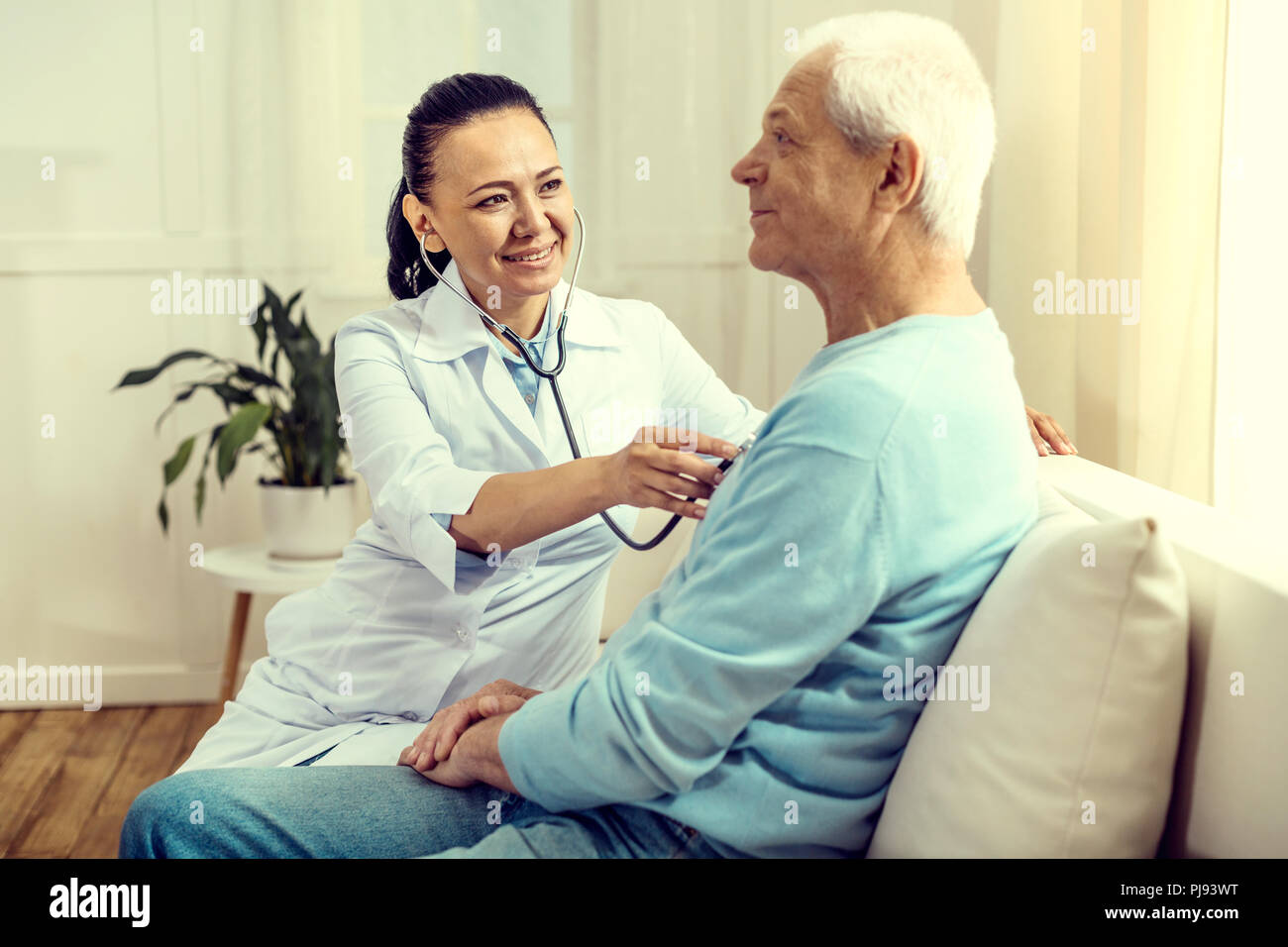 Cheerful doctor using stethoscope for checking lungs of elderly man - Stock Image