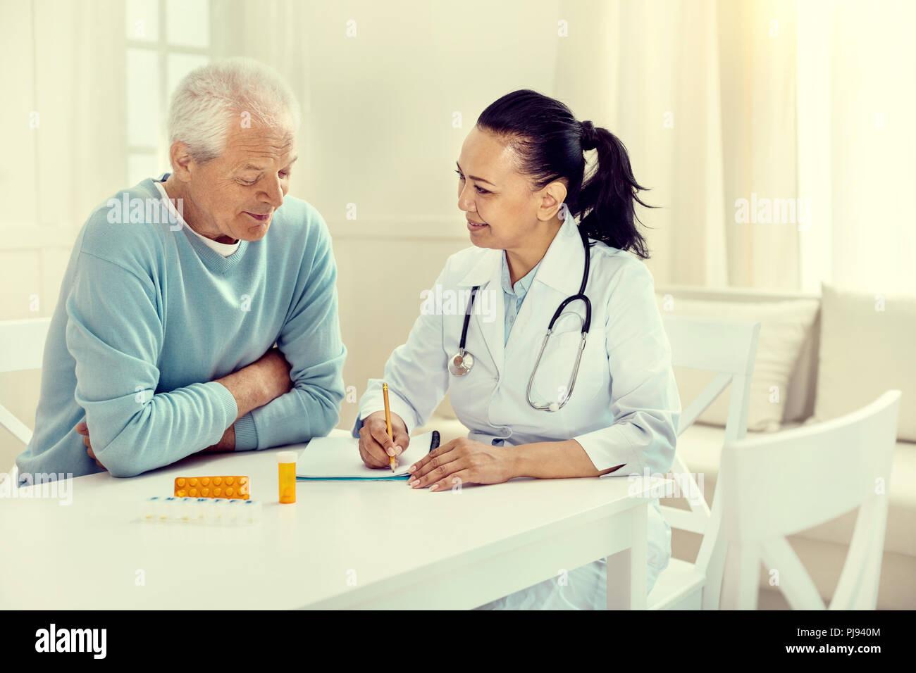 Cheerful doctor and retired gentleman discussing regimen - Stock Image