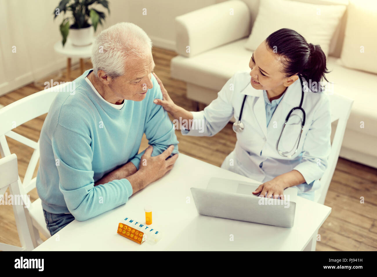 Mindful nurse cheering retired patient and smiling - Stock Image