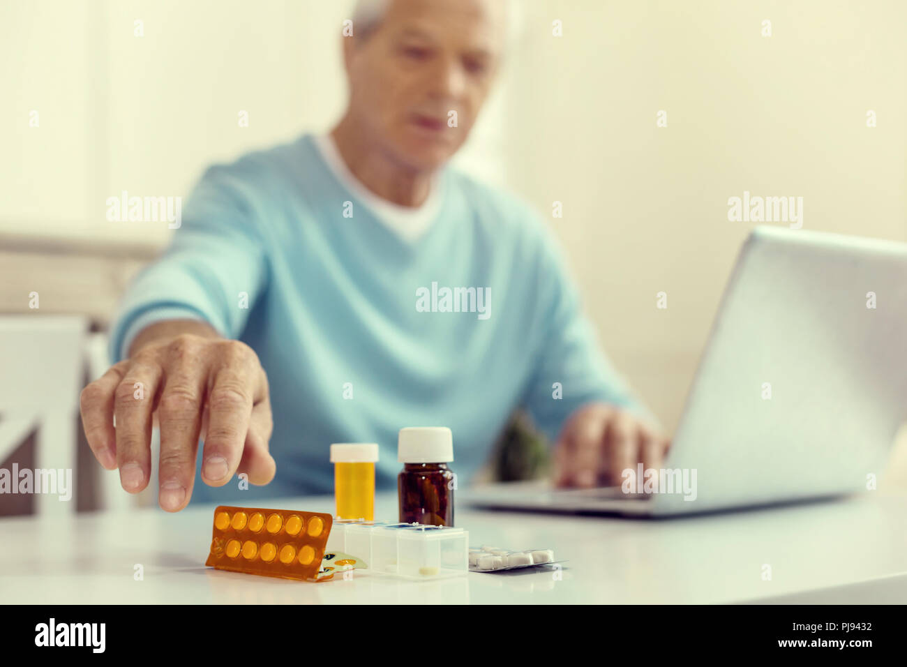 Close up of male hand reaching for medication - Stock Image