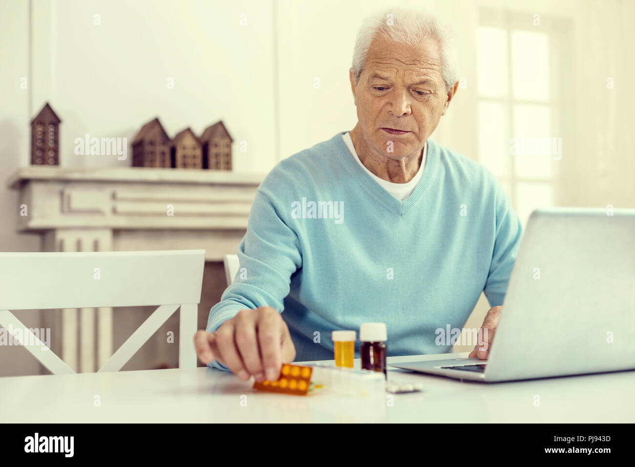 Upset retired man taking his pills while working on laptop - Stock Image