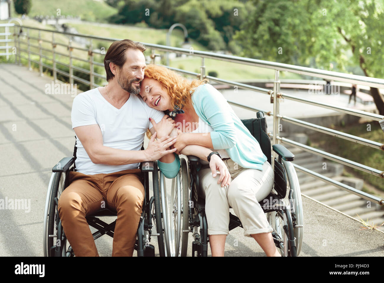 Loving wife laughing and embracing husband - Stock Image
