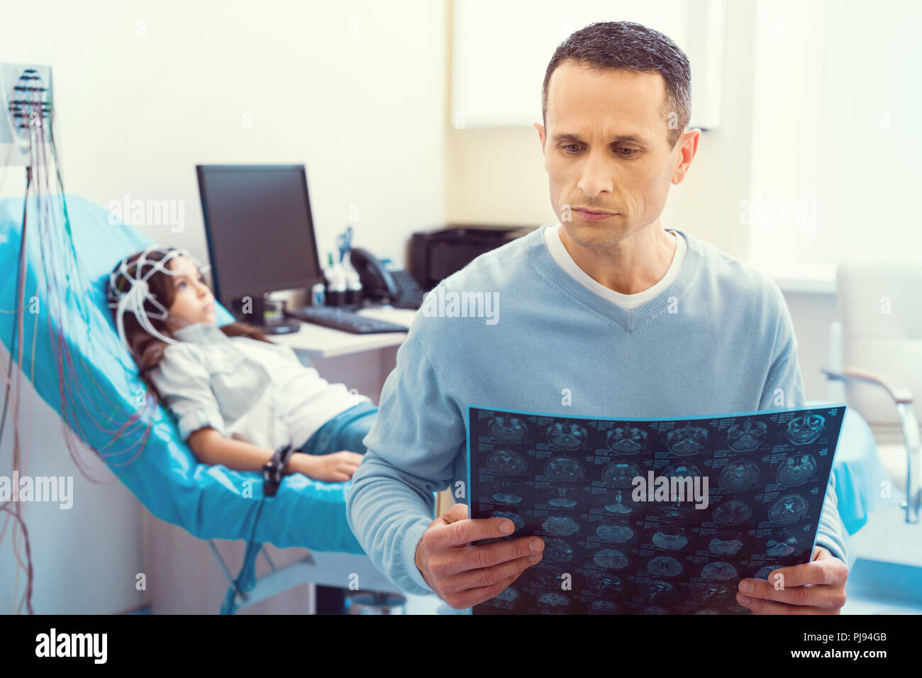 Worried parent examining mri scan of his poor daughter - Stock Image