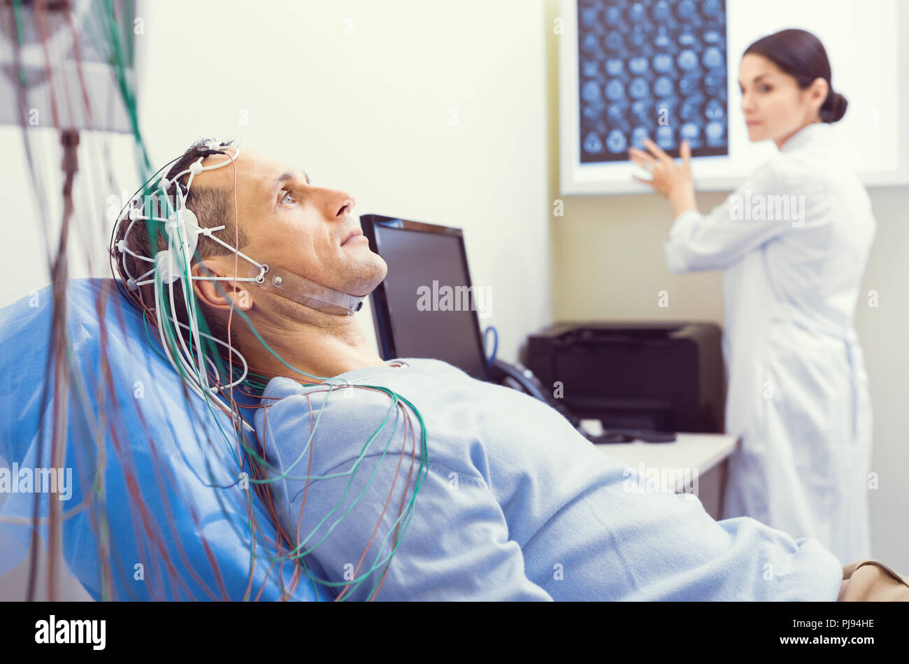 Nervous gentleman getting brain analyzed by electroencephalography machine - Stock Image