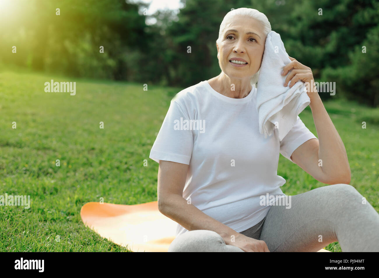 Exhausted retired woman recharging her batteries after exercising - Stock Image