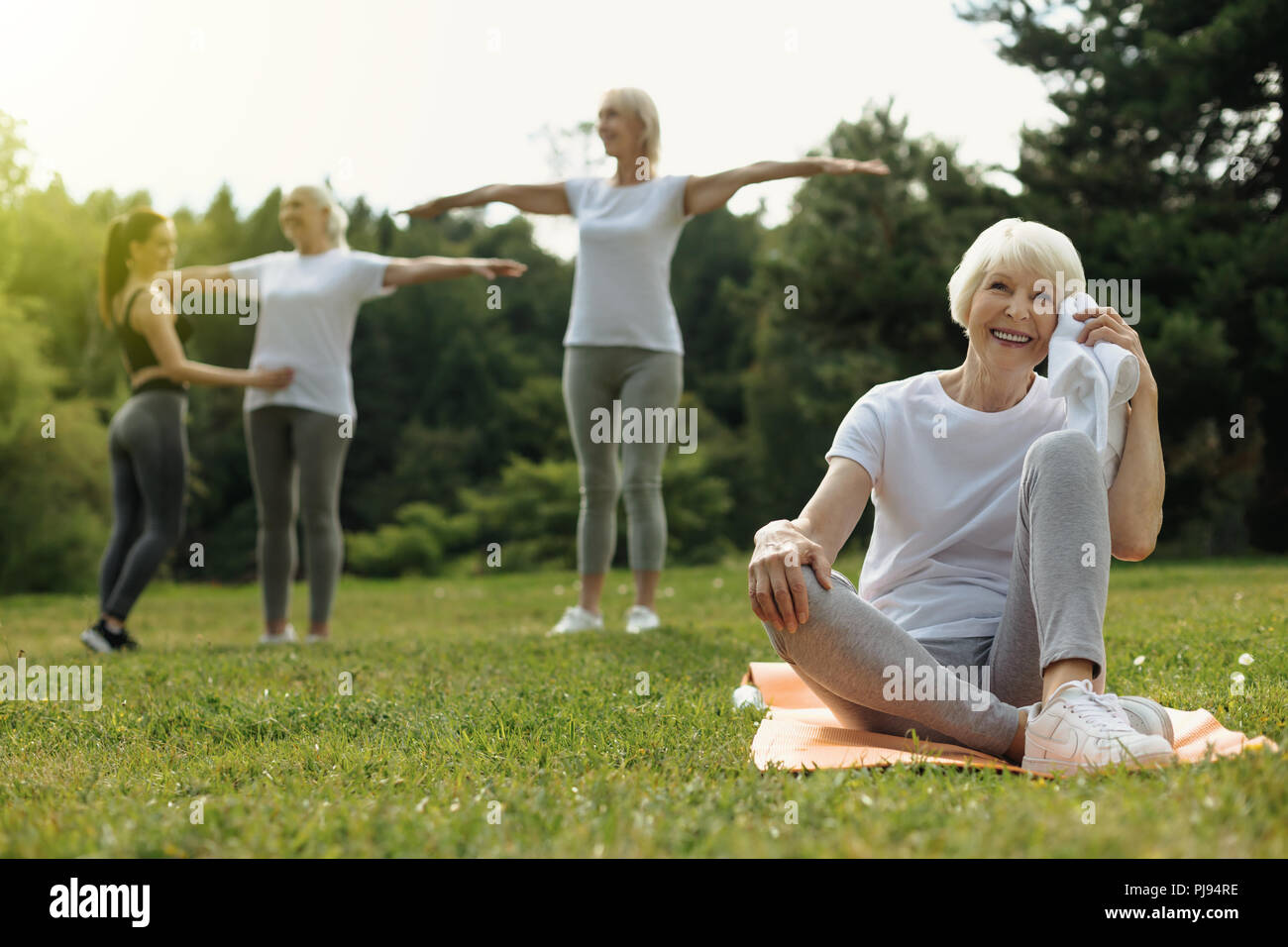 Happy retired woman beaming after exercising outdoors - Stock Image
