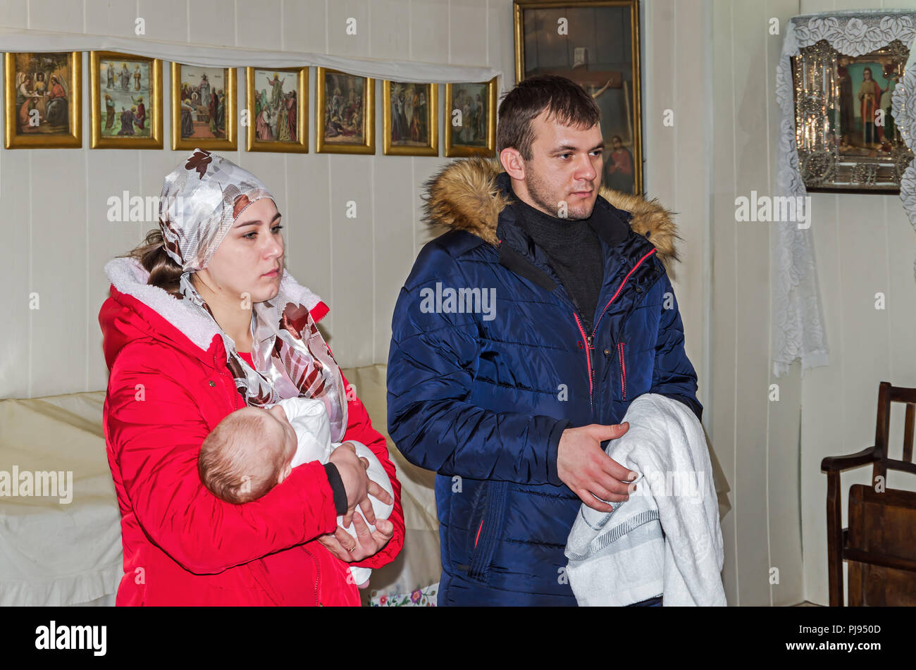 Godfather and godmother are keep in arms of child during the rite of christening in the Orthodox Church - Stock Image