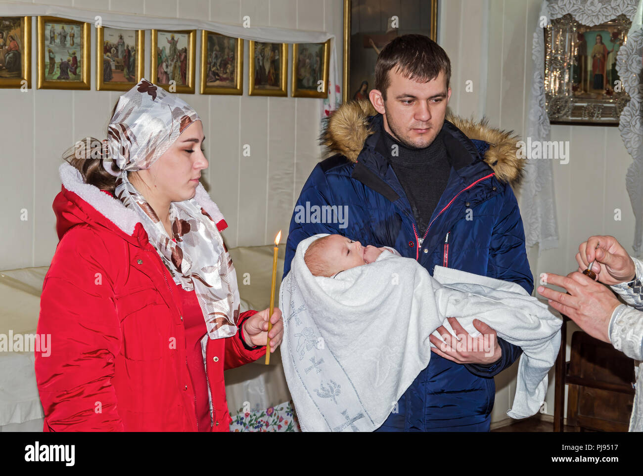 Godfather and godmother are keep in arms of child during the rite of baptism in the Orthodox Church - Stock Image